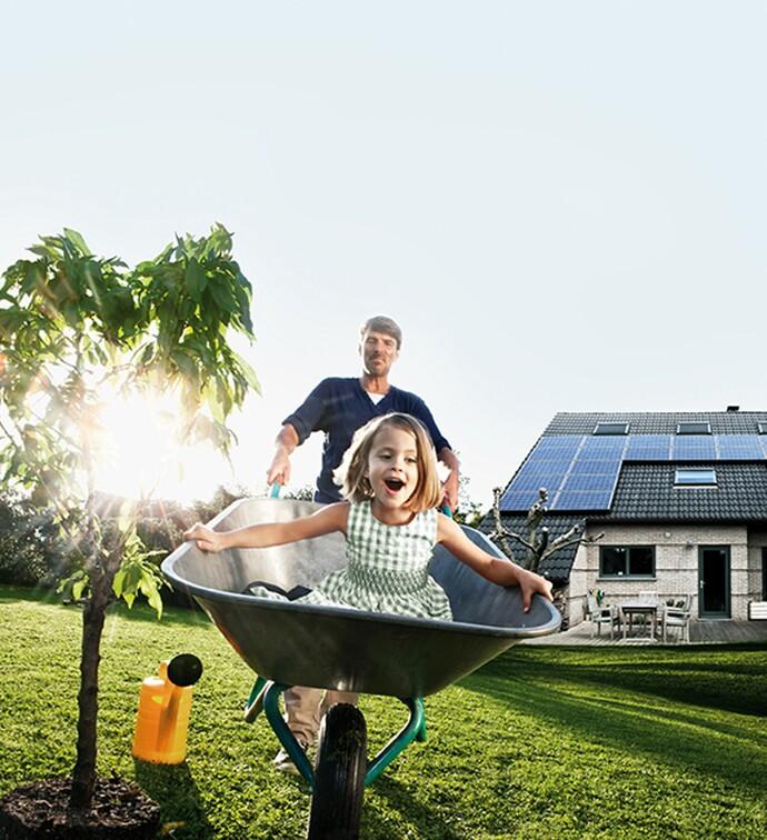 un homme et sa fille jouent dans le jardin.