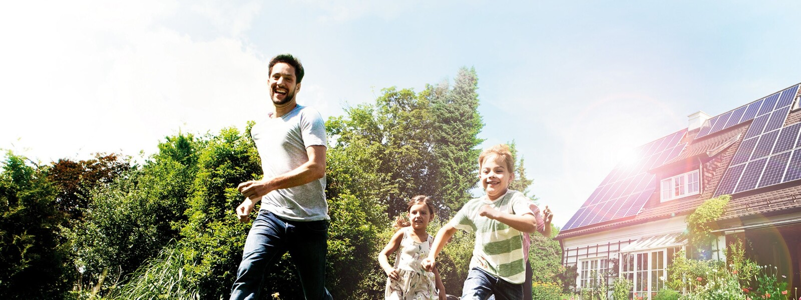 un homme court dans le jardin avec ses enfants